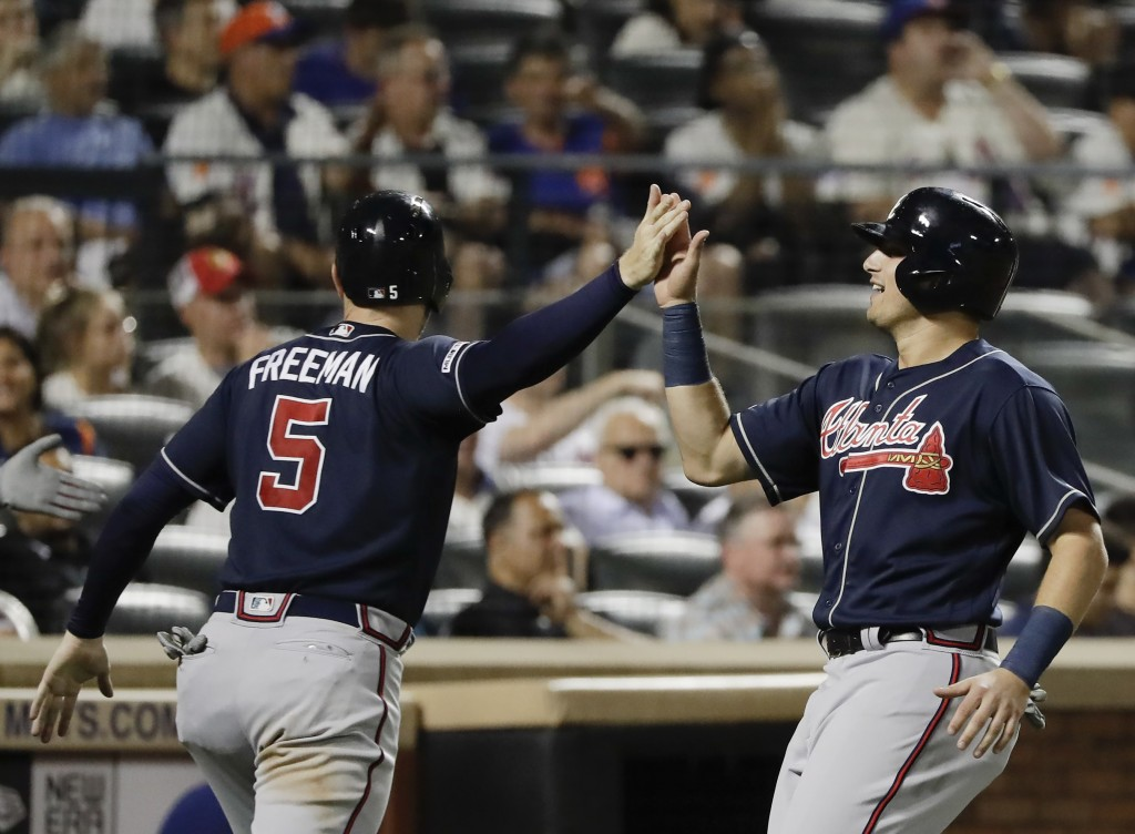 Atlanta Braves' Austin Riley, right, celebrates with teammate Freddie Freeman, left, after they scored on a three-run double by Johan Camargo during t...