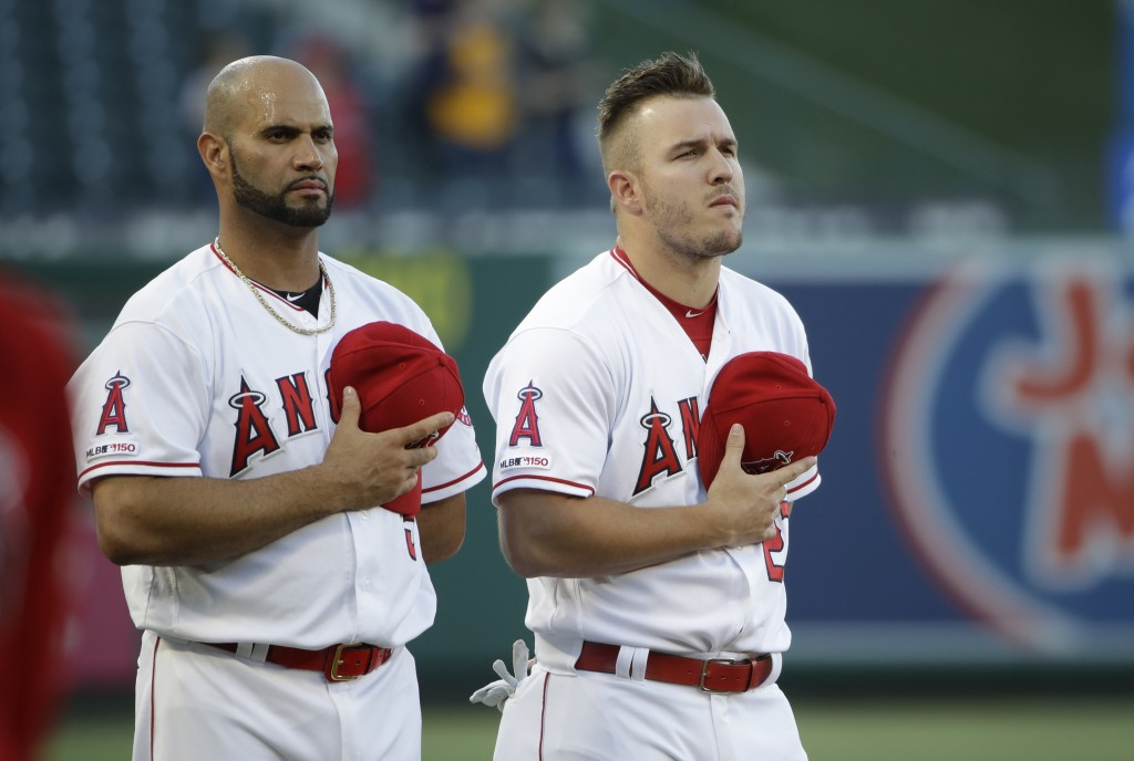 Los Angeles Angels' Albert Pujols, left, and Mike Trout listen to the national anthem before the team's baseball game against the Oakland Athletics on...