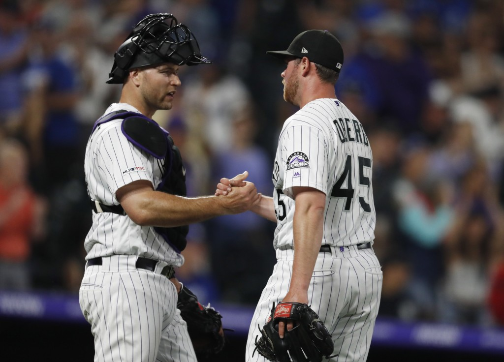Colorado Rockies catcher Chris Iannetta, left, congratulates relief pitcher Scott Oberg, who stuck out Los Angeles Dodgers pinch-hitter Edwin Rios for...