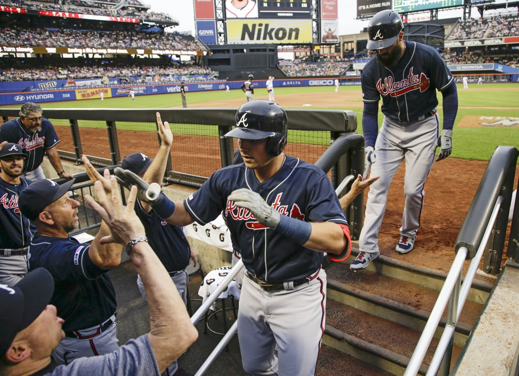 Atlanta Braves' Austin Riley, center, celebrates with teammates after hitting a two-run home run during the second inning of a baseball game against t...