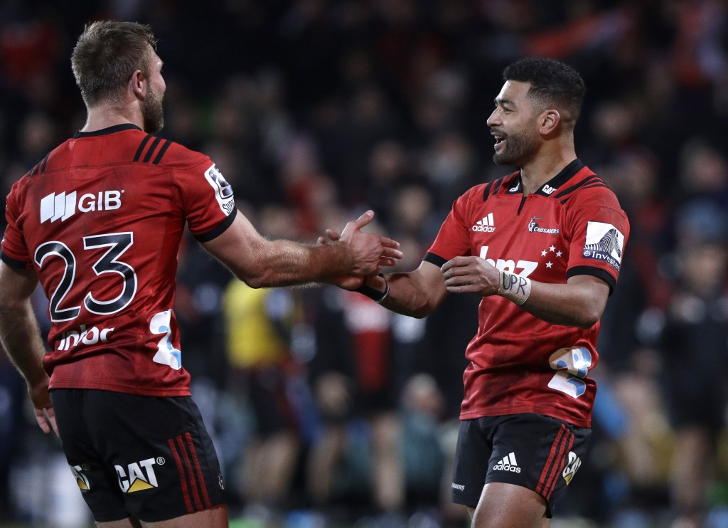 Crusaders Richie Mo'unga, right, and teammate Braydon Ennor celebrate after defeating the Hurricanes in their Super Rugby semifinal in Christchurch, N...