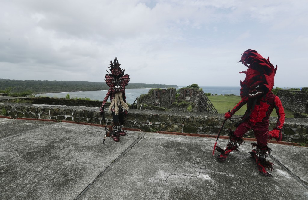 Men wearing Devil costumes dance on a wall of Fort San Lorenzo, on a promontory overlooking the mouth of the Chagres River, on Panama's Caribbean coas...