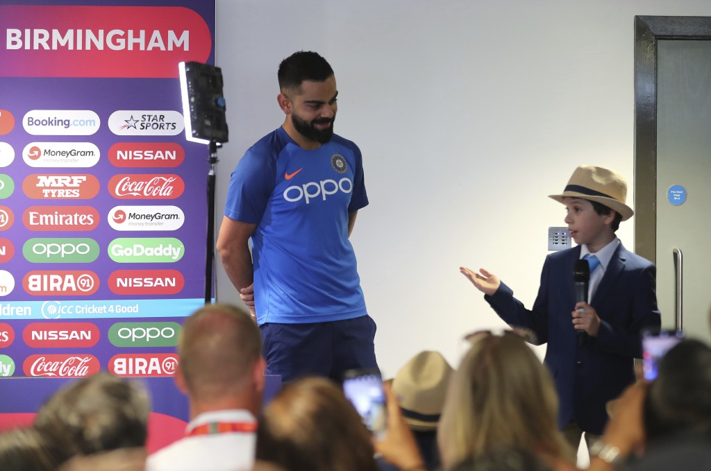 Nine-year old Edward William, right, introduces India's captain Virat Kohli, left, to journalists as part of a fundraising event OneDay4Children befor...