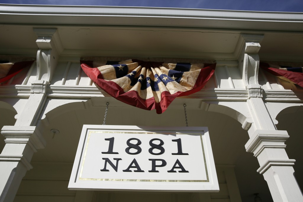 In this photo taken Wednesday, June 5, 2019, a sign and bunting hangs over the entrance to 1881 Napa in Oakville, Calif. 1881 Napa, a wine history mus...