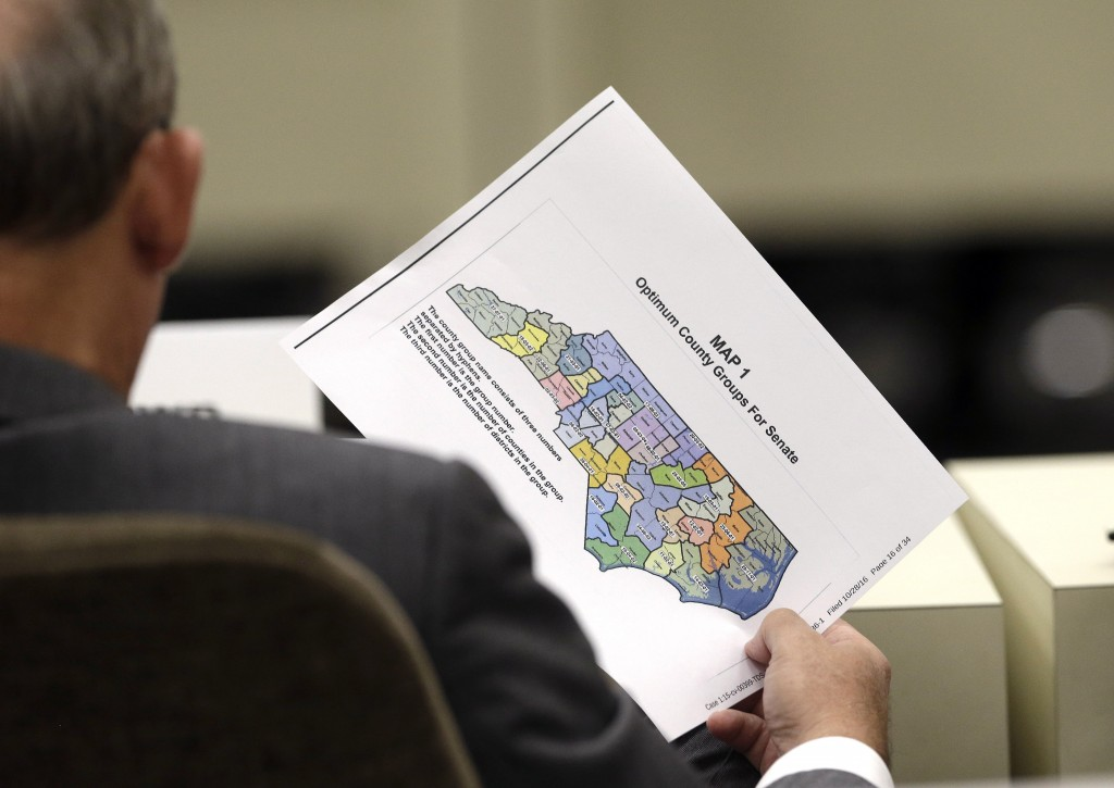 In this photo taken Wednesday, July 26, 2017 a lawmaker holds a districting map during a joint select committee meeting on redistricting in Raleigh, N...