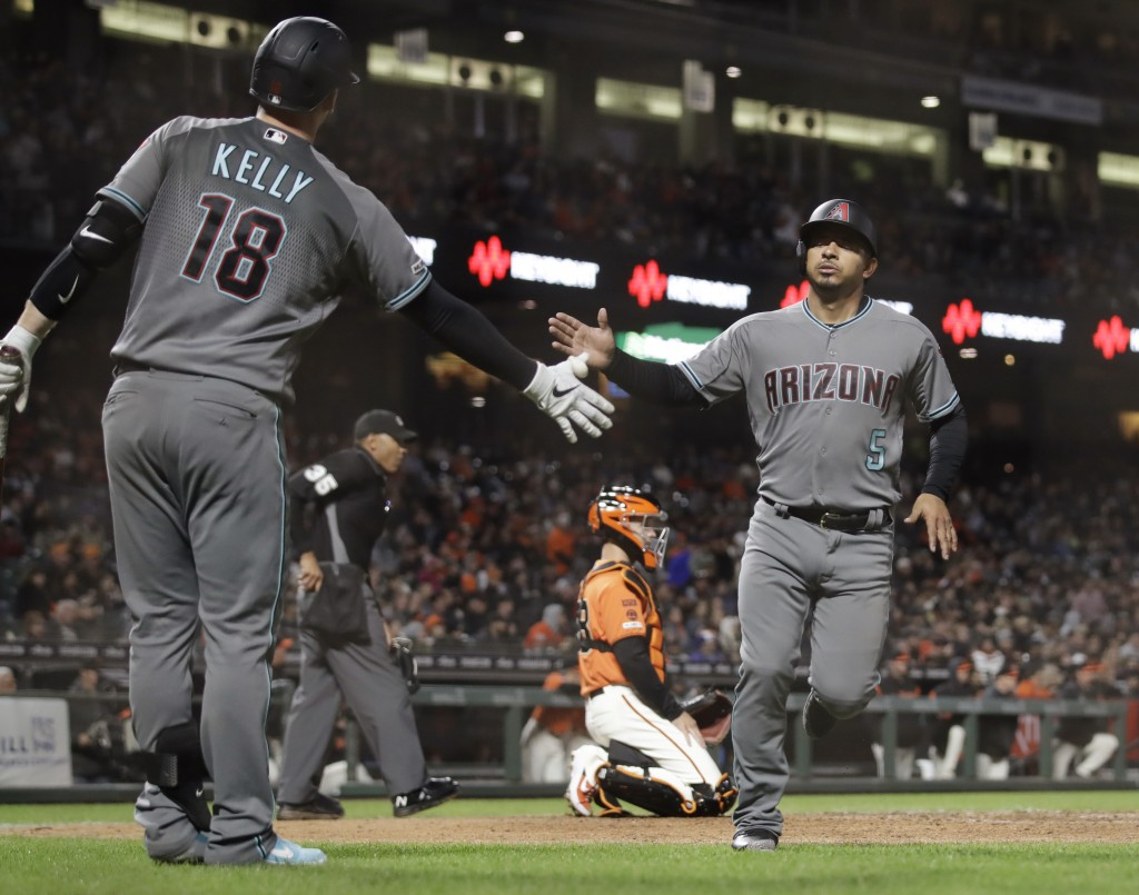 Arizona Diamondbacks' Eduardo Escobar, right, is congratulated by Carson Kelly after scoring against the San Francisco Giants during the sixth inning ...