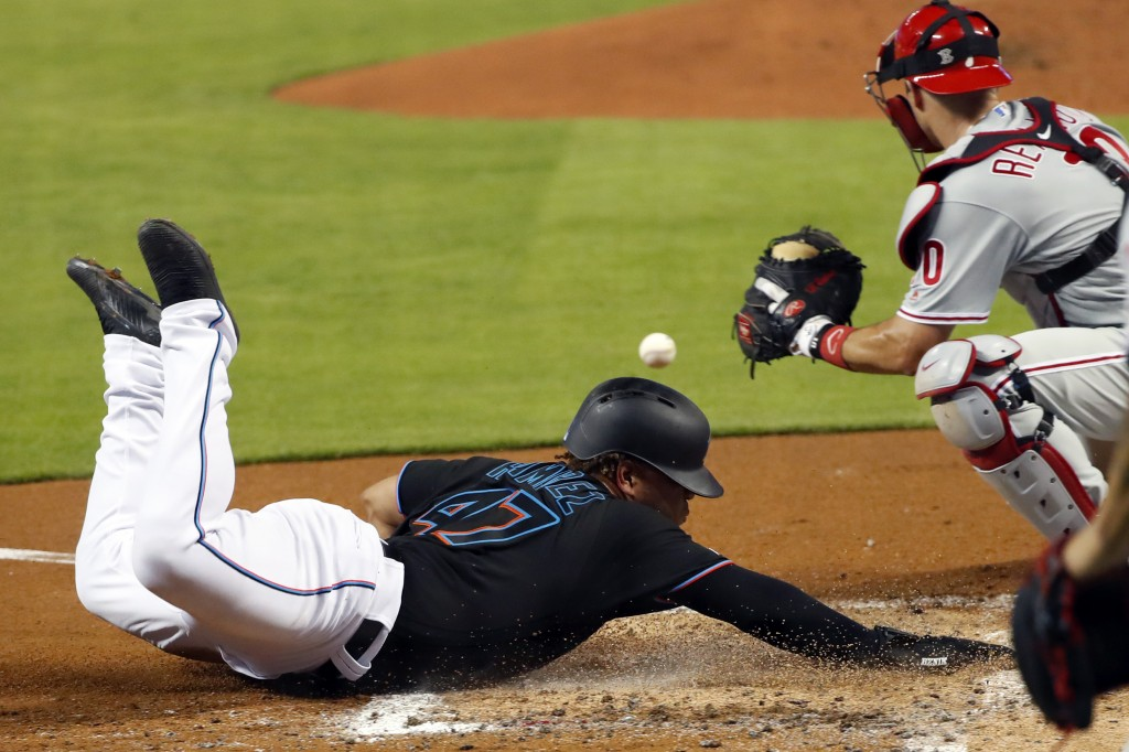 Miami Marlins' Harold Ramirez (47) scores on a Brian Anderson double as Philadelphia Phillies catcher J.T. Realmuto (10) waits for the throw during th...