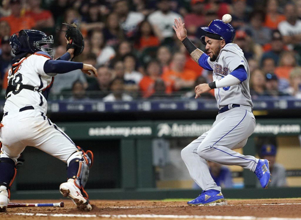 Houston Astros catcher Robinson Chirinos (28) reaches for the ball to tag out Seattle Mariners' J.P. Crawford during the fourth inning of a baseball g...