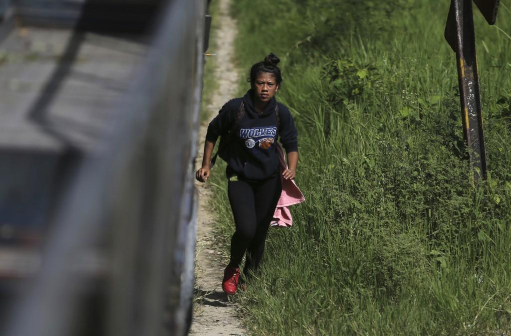 In this June 25, 2019 photo, 19-year-old Honduran Saily Yasmín Andino runs to climb aboard a freight train, near Salto de Agua, Mexico. Hours later th...