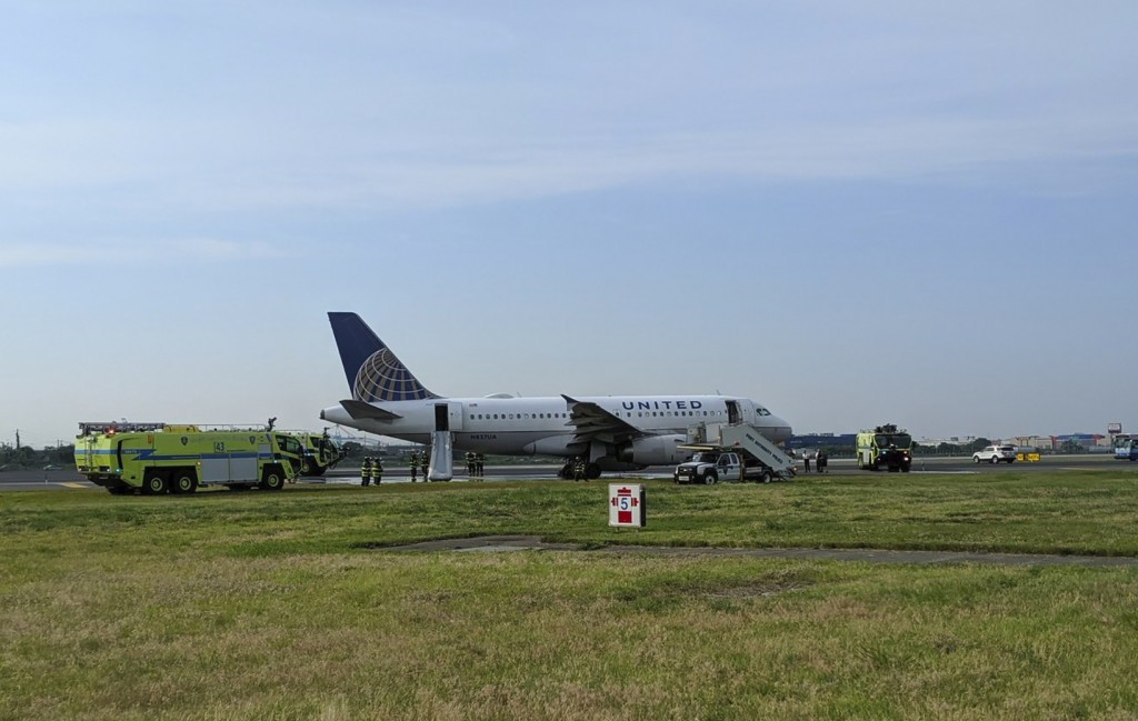 This photo provided by John Murray shows a United flight sitting on the runway after making an emergency landing, Saturday, June 29, 2019 at Newark Li...