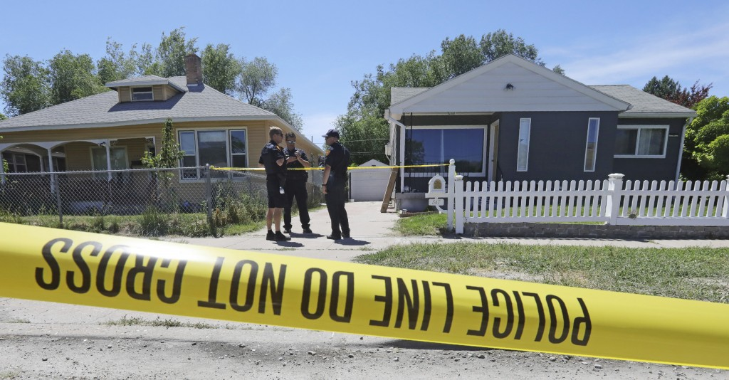 Police officers stand in front of the home, right, of Ayoola A. Ajayi Friday, June 28, 2019, in Salt Lake City. Authorities are filing murder and kidn...