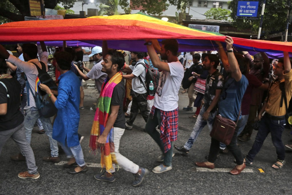 Gay rights activists walk with a rainbow colored flag during a rally to commemorate the twentieth anniversary of the first pride parade in the country...