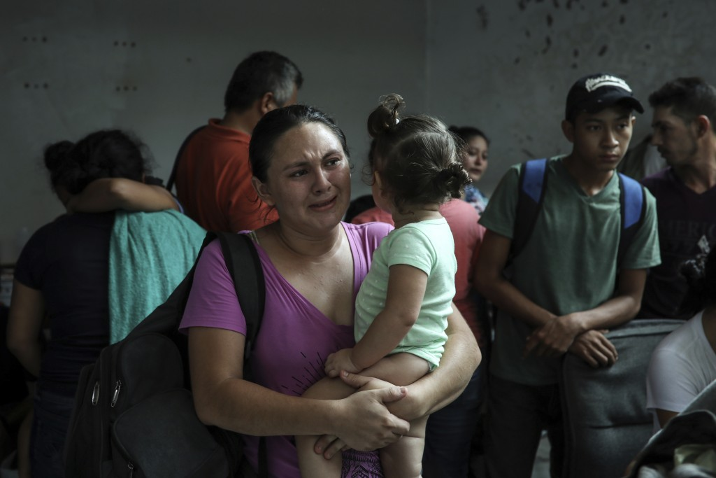 Detained migrants stand together in a storage room at the back of the Azteca Hotel where they tried to hide from  Mexican immigration agents conductin...
