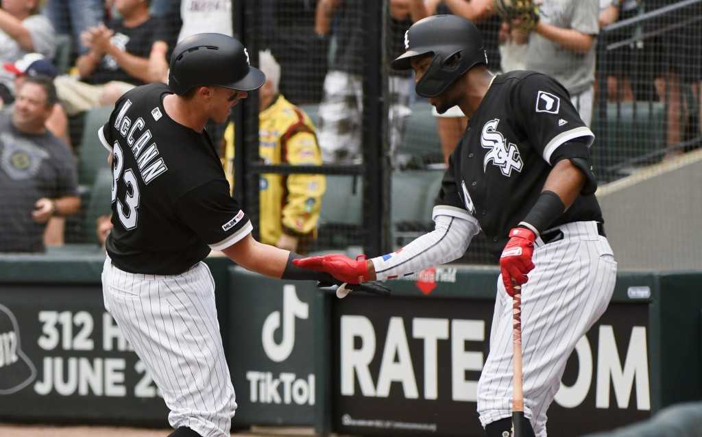 Chicago White Sox's James McCann (33) celebrates with Eloy Jimenez, right, after McCann hit a two-run home run during the first inning of a baseball g...