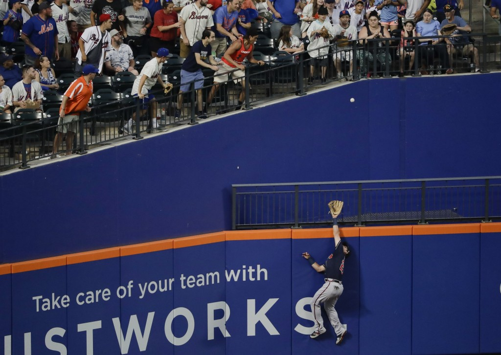 Fans watch as Atlanta Braves' Austin Riley chases a ball hit by New York Mets' Pete Alonso for a home run during the fourth inning of a baseball game ...