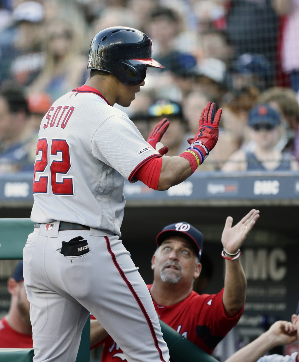 Washington Nationals' Juan Soto (22) is congratulated by pitching coach Paul Menhart after hitting a solo home run against the Detroit Tigers during t...
