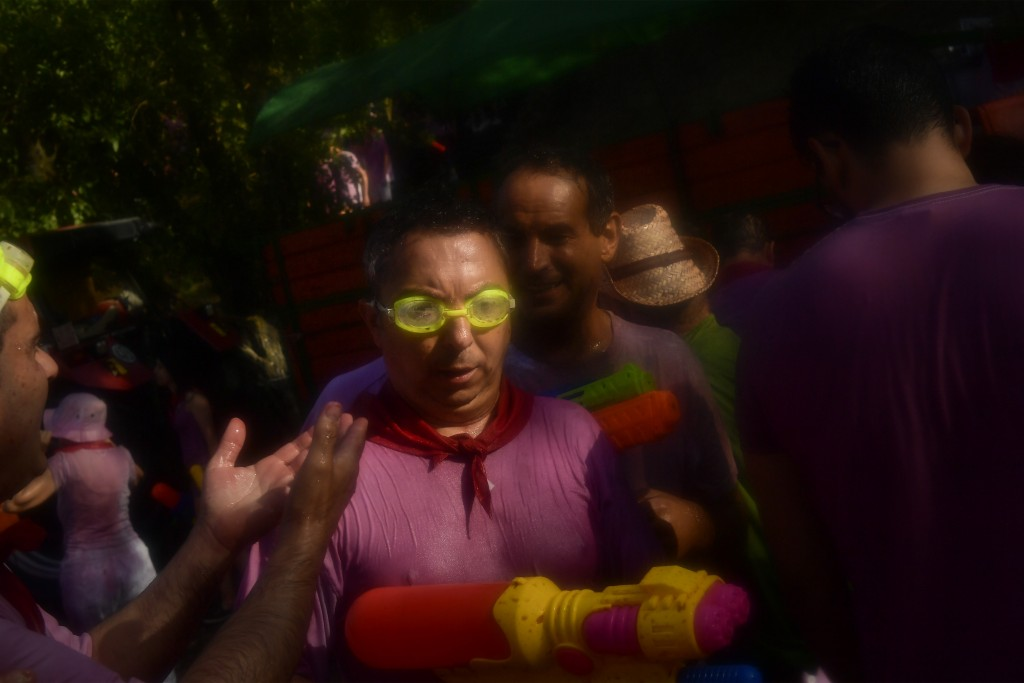 A reveler protects her eyes while taking part in a wine battle, in the small village of Haro, northern Spain, Saturday, June 29, 2019. Hundreds of rev...