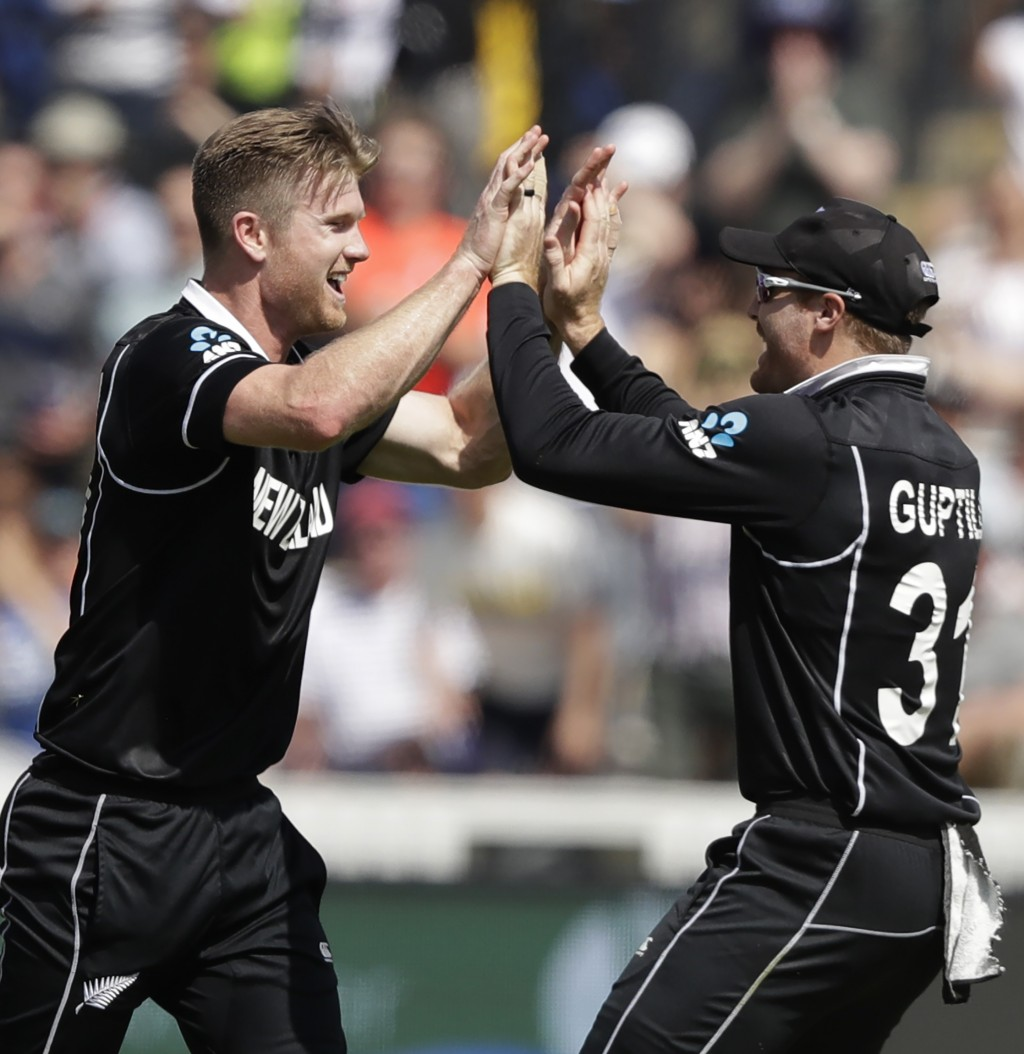 New Zealand's James Neesham, left, celebrates with teammate New Zealand's Martin Guptill after taking the wicket of Australia's Glenn Maxwell caught a...