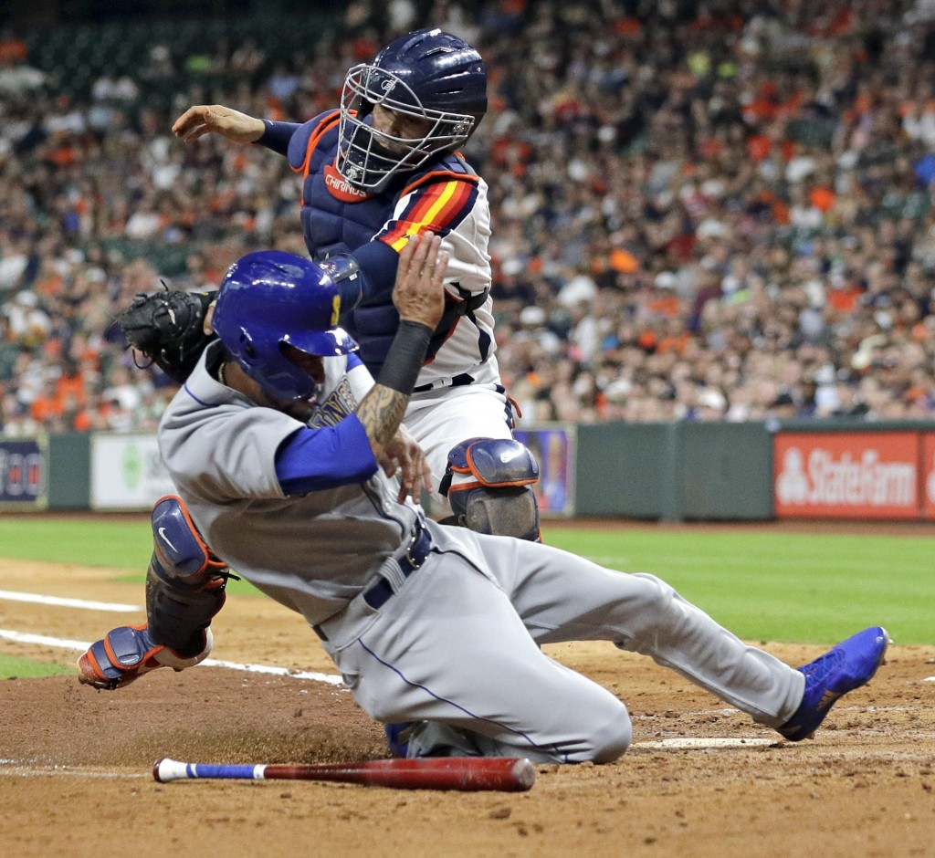 Seattle Mariners' J.P. Crawford, bottom, is tagged out by Houston Astros catcher Robinson Chirinos, while trying to score during the fourth inning of ...