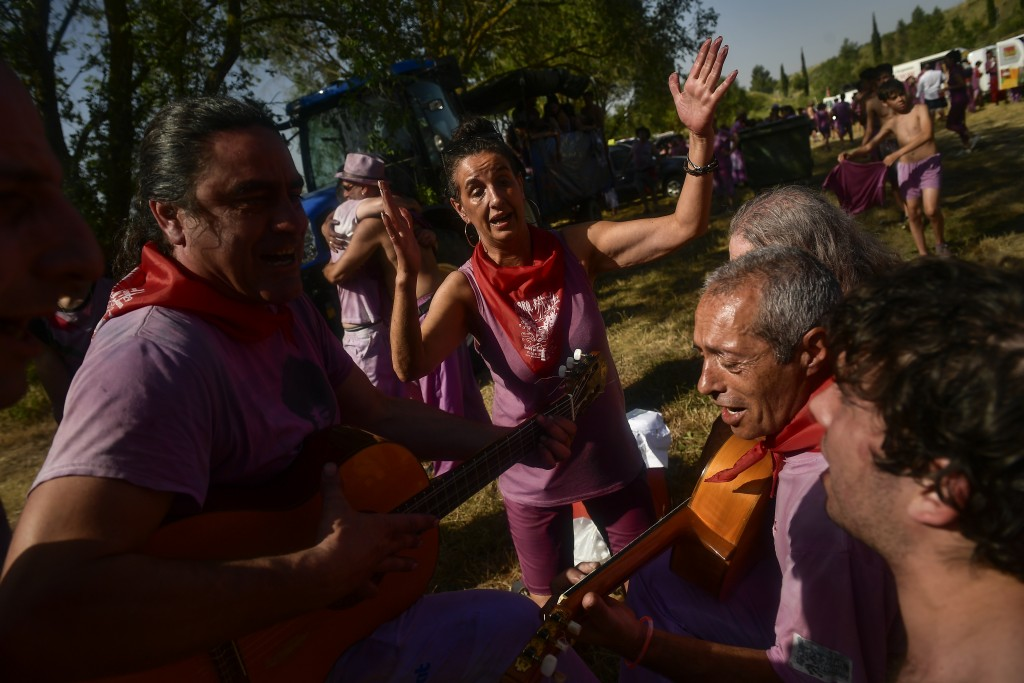 People sing a song at the end of wine battle, in the small village of Haro, northern Spain, Saturday, June 29, 2019. Hundreds of revelers participate ...