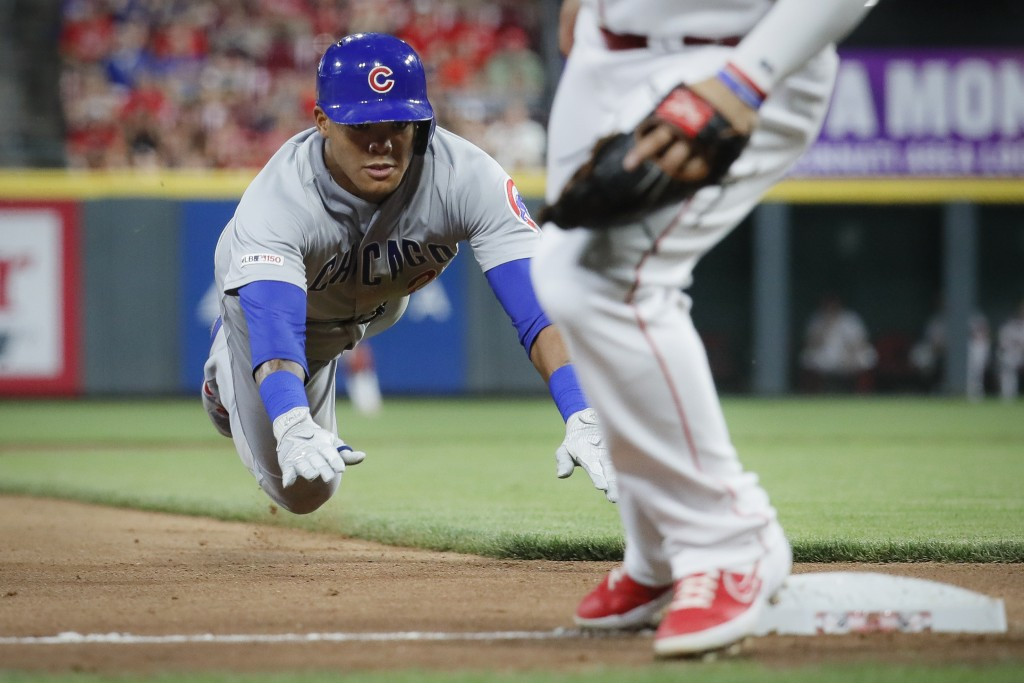 Chicago Cubs' Addison Russell slides into third with a triple off Cincinnati Reds relief pitcher David Hernandez during the seventh inning of a baseba...