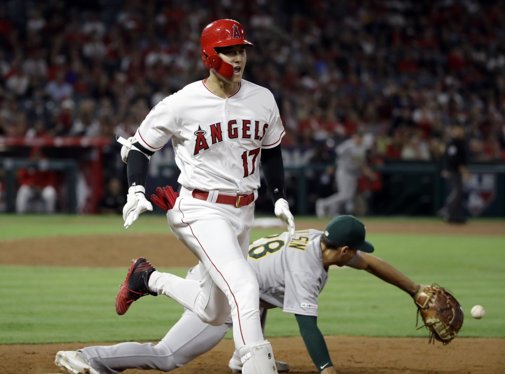 Los Angeles Angels' Shohei Ohtani (17) reaches first base with an infield single next to Oakland Athletics' Matt Olson during the sixth inning of a ba...