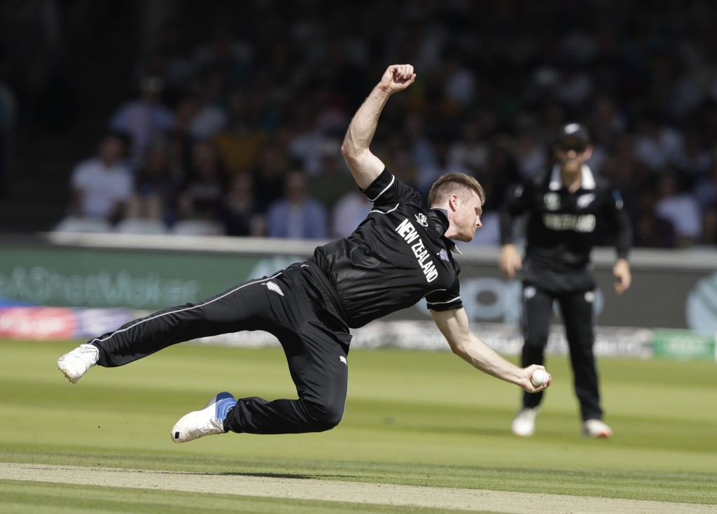 New Zealand's James Neesham dives to his left to dismiss caught and bowled Australia's Glenn Maxwell during the Cricket World Cup match between New Ze...