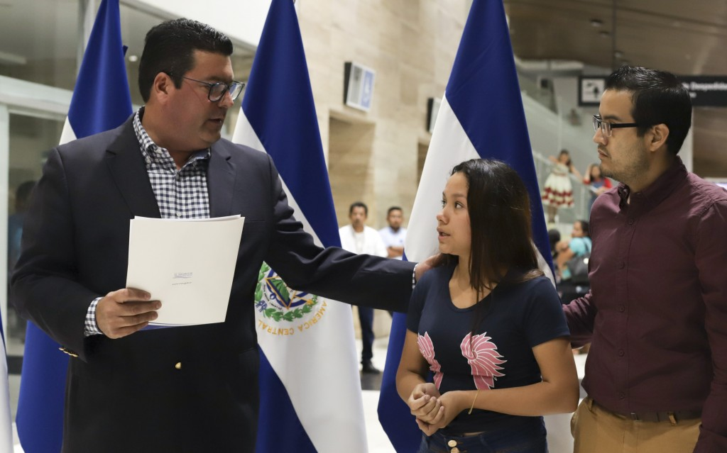 Tania Vanessa Avalos talks with the Deputy Minister for Salvadorans Abroad, left, during a press conference at the airport, after her arrival in San S...