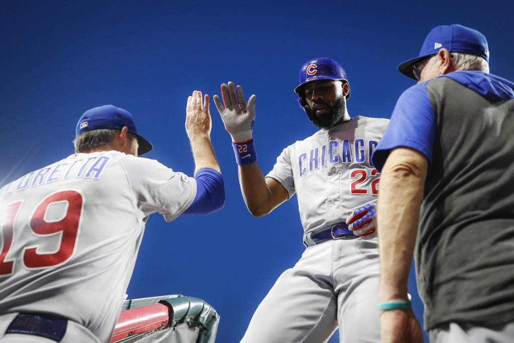 Chicago Cubs' Jason Heyward, center, celebrates at the dugout steps after hitting a two-run home run off Cincinnati Reds starting pitcher Sonny Gray d...