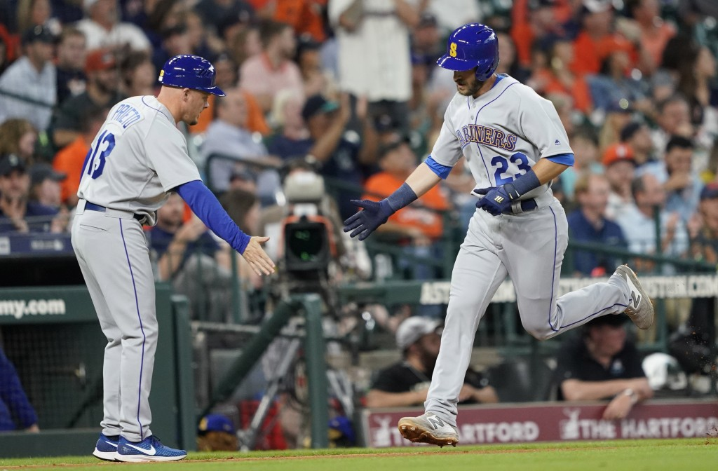 Seattle Mariners' Austin Nola (23) is congratulated by third base coach Chris Prieto after hitting a home run against the Houston Astros during the th...
