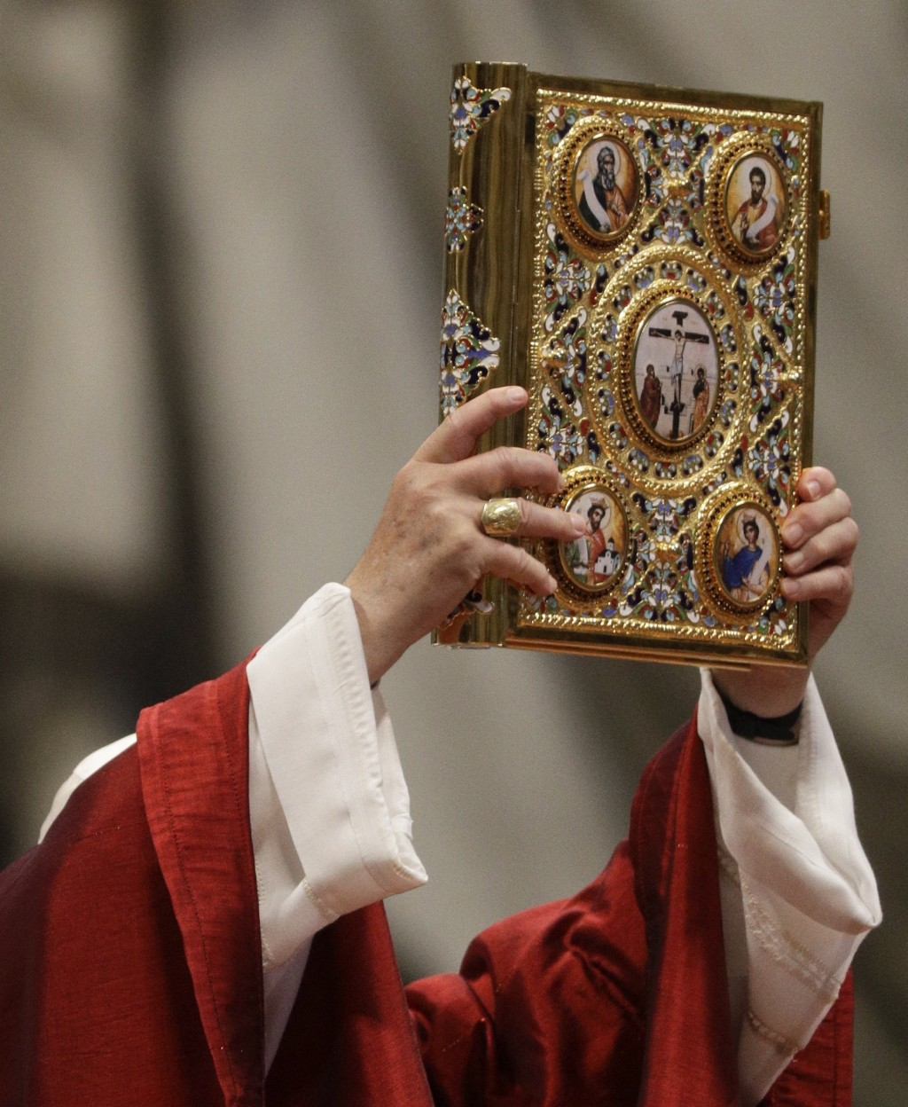 Pope Francis holds up the book of Gospels as he celebrates Mass in St. Peter's Basilica at the Vatican, Saturday, June 29, 2019. (AP Photo/Gregorio Bo...