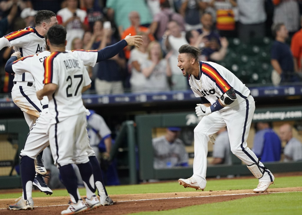 Houston Astros' Yuli Gurriel, right, celebrates with teammates after hitting a game-winning home run against the Seattle Mariners during the 10th inni...