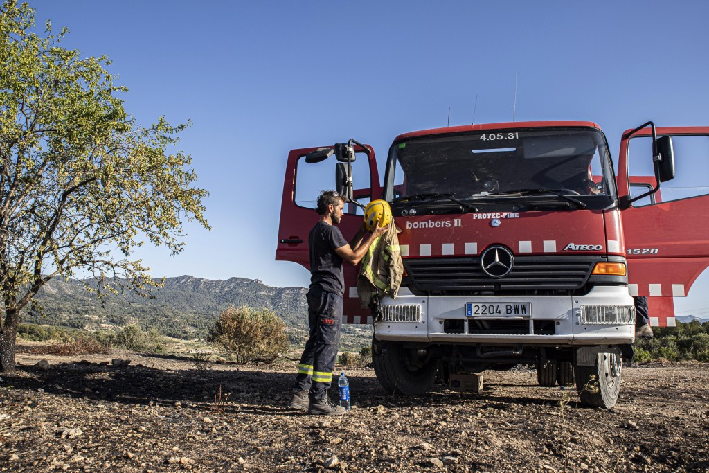 A firefighter stands by a fire truck in La Palma d'Ebre, Spain, Friday June 28, 2019. A major wildfire in northeastern Spain that began in a pile of c...