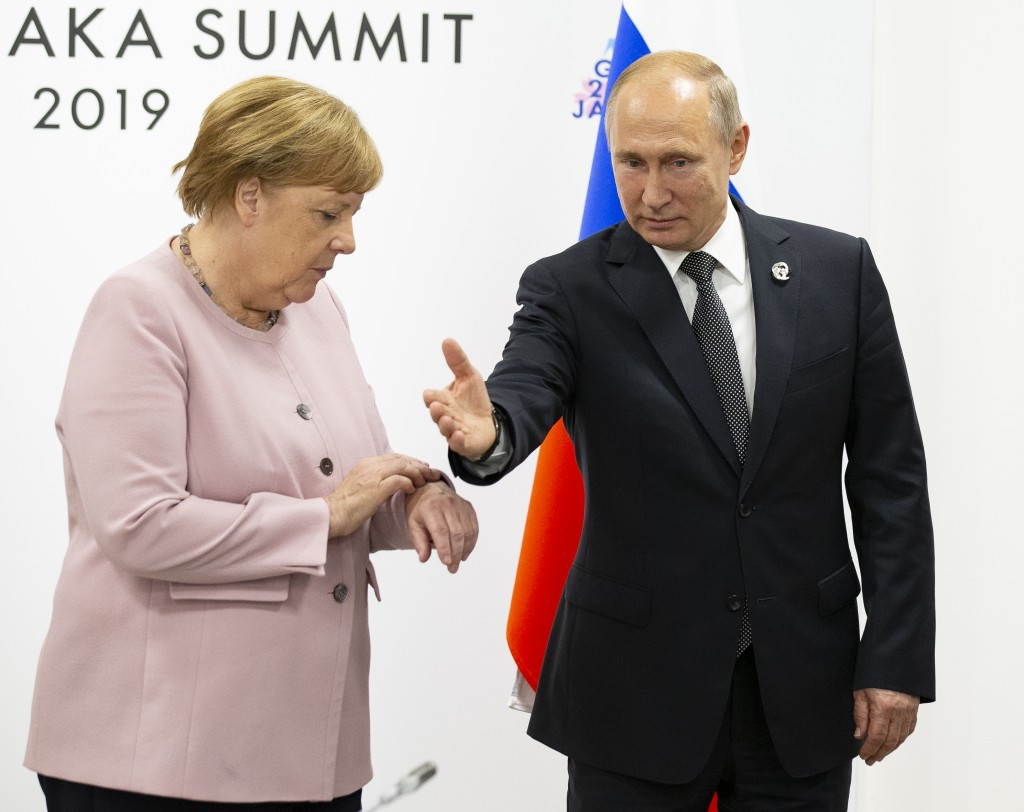 German Chancellor Angela Merkel, left, looks at her watch as Russian President Vladimir Putin visits her for the talks during a meeting on the sidelin...