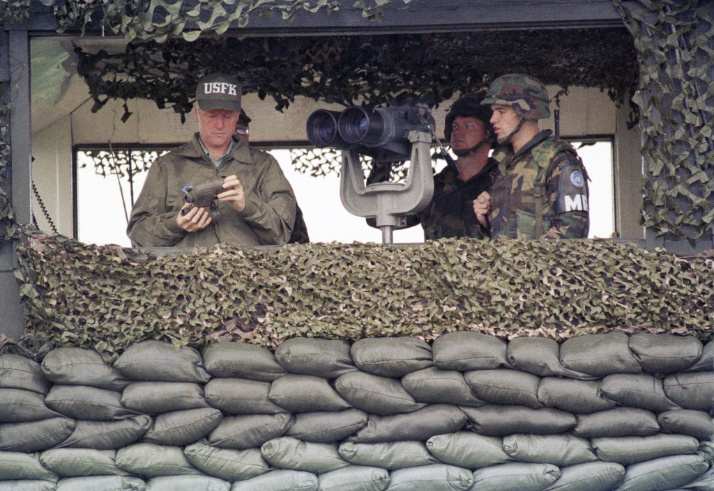 FILE - In this July 11, 1993, file photo, U.S. President Bill Clinton takes the lens caps off a pair of binoculars at Camp Casey from the Ouellette gu...