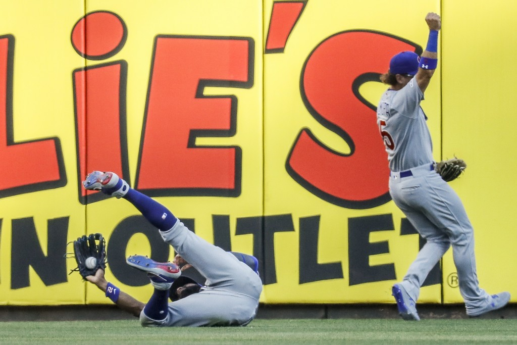 Chicago Cubs right fielder Jason Heyward, left, catches a fly ball by Cincinnati Reds' Nick Senzel for an out in the first inning of a baseball game, ...