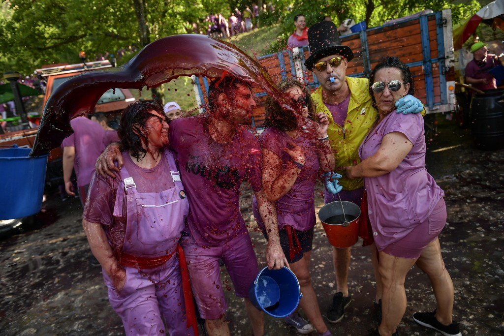 Revelers are covered in wine as people take part in a wine battle, in the small village of Haro, northern Spain, Saturday, June 29, 2019. Hundreds of ...