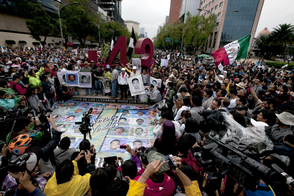 In this April 26, 2015 file photo, parents and classmates of the 43 missing students from Ayotzinapa hold posters for the press to see, of their missi...