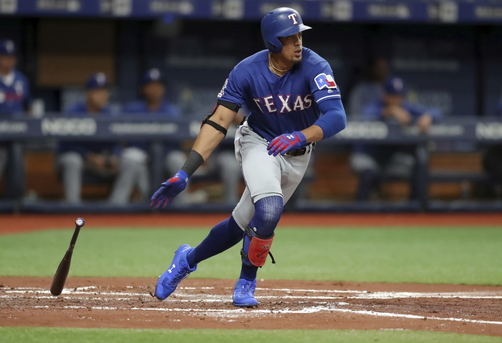 Texas Rangers' Ronald Guzman drops his bat after hitting a two-run double against the Tampa Bay Rays during the second inning of a baseball game Frida...