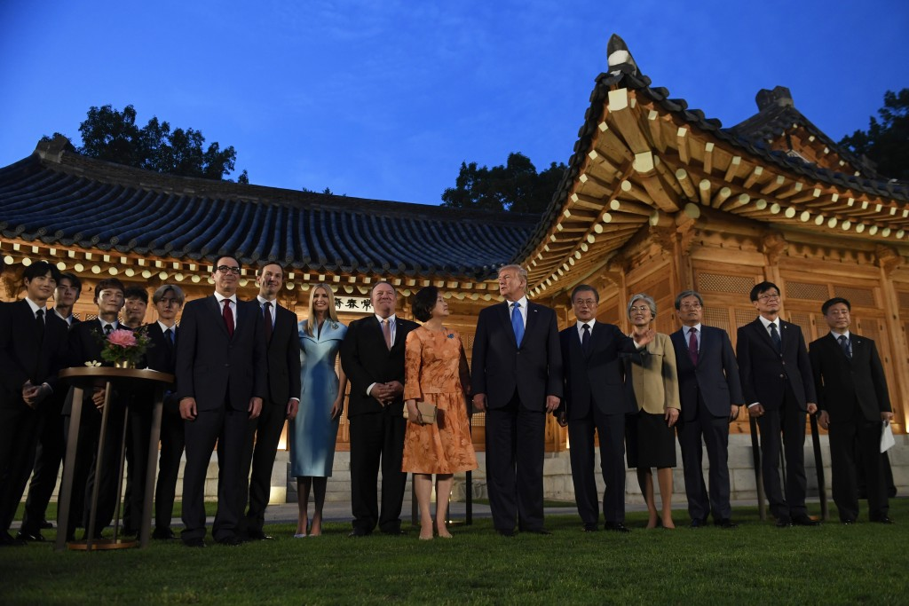President Donald Trump, center, and South Korean President Moon Jae-in, fifth right, pose for a group photo with guests during a visit to the tea hous...