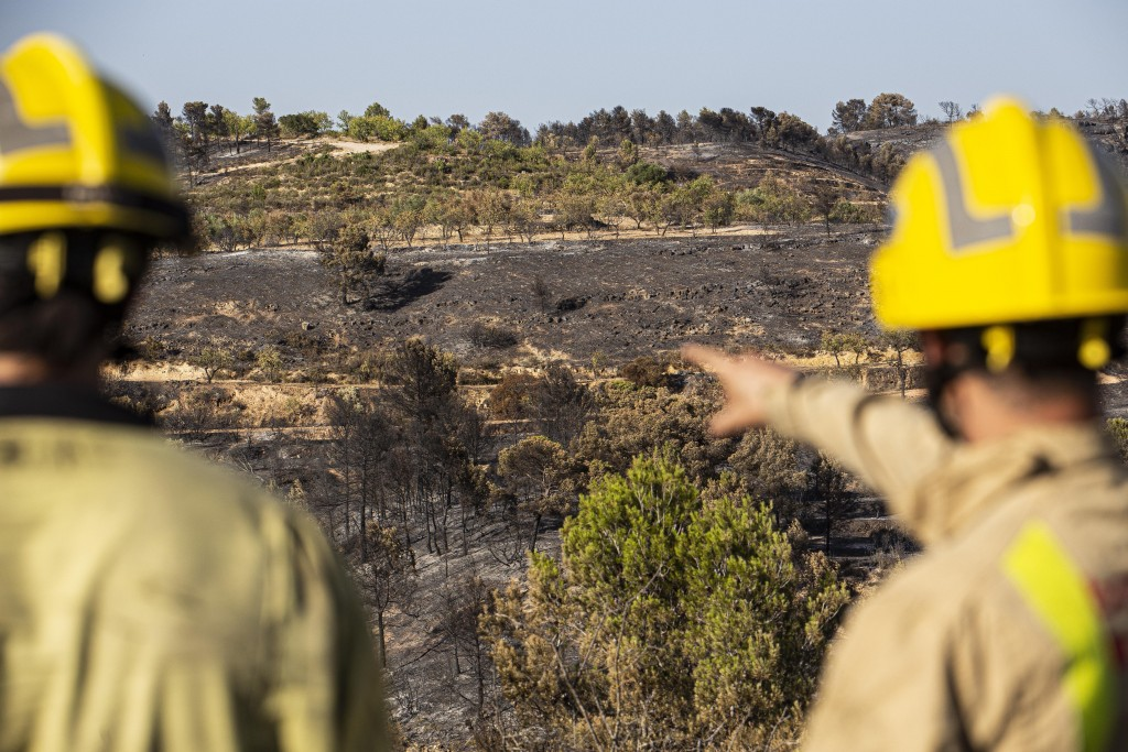Two firefighters look at burned terrain in La Palma d'Ebre, Spain, Friday June 28, 2019. A major wildfire in northeastern Spain that began in a pile o...