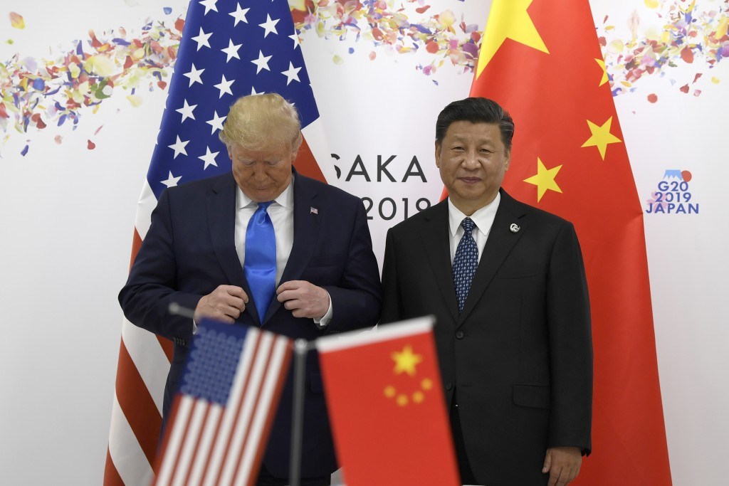 President Donald Trump adjusts his jacket as he poses for a photo with Chinese President Xi Jinping during a meeting on the sidelines of the G-20 summ