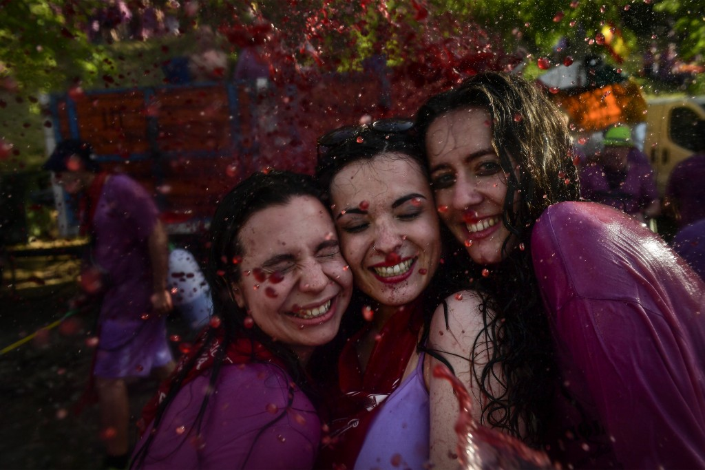 Revelers smile while taking part in a wine battle, in the small village of Haro, northern Spain, Saturday, June 29, 2019. Hundreds of revelers partici...
