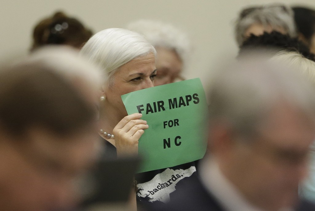 In this photo taken Wednesday, July 26, 2017 a member of the gallery tries to display her sign while lawmakers convene during a joint select committee...
