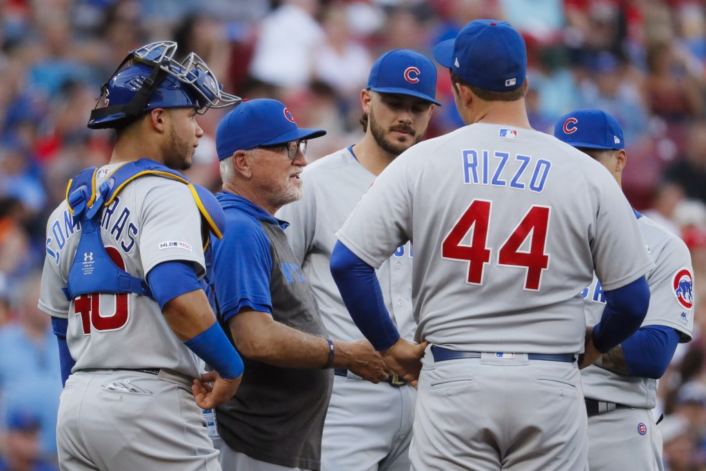 Chicago Cubs manager Joe Maddon, second from left, meets his players on the mound after removing starting pitcher Cole Hamels during the second inning...