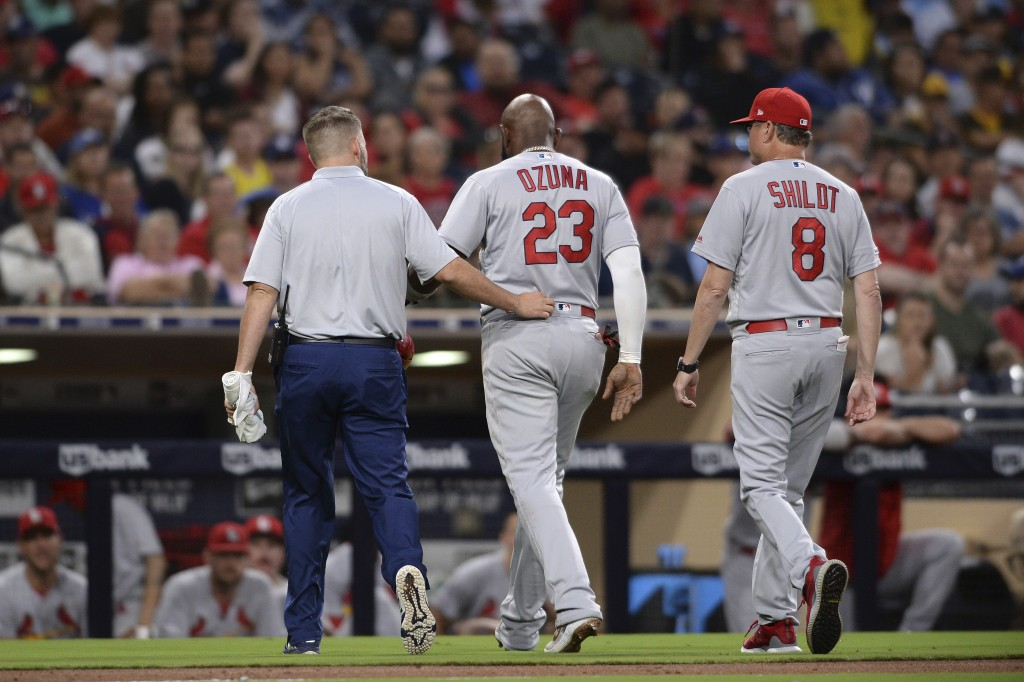 St. Louis Cardinals' Marcell Ozuna, center, leaves the field accompanied by a trainer and Mike Shildt during the third inning of a baseball game again...