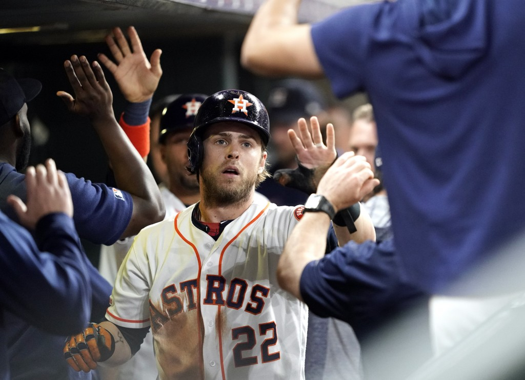 Houston Astros' Josh Reddick (22) celebrates with teammates in the dugout after scoring against the Seattle Mariners during the second inning of a bas...