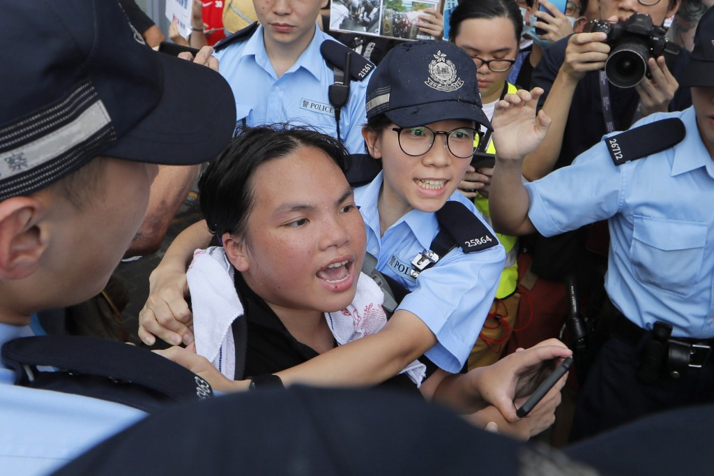 A pro-democracy protester is stopped by police officers as she argues with pro-China's supporters during a rally outside Legislative Council Complex i...