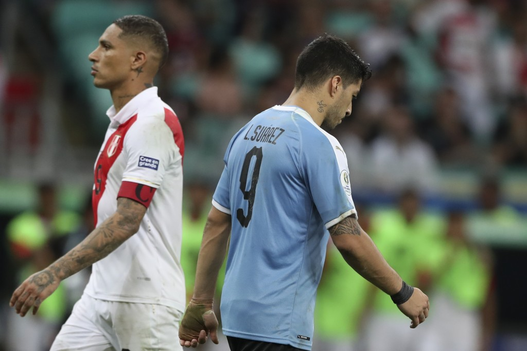 Uruguay's Luis Suarez, right, walks by Peru's Paolo Guerrero, left, after failing to score during the penalty shoot-out during a Copa America quarterf...