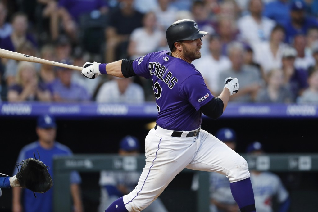 Colorado Rockies' Mark Reynolds follows through on a two-run single off Los Angeles Dodgers starting pitcher Clayton Kershaw during the sixth inning o...